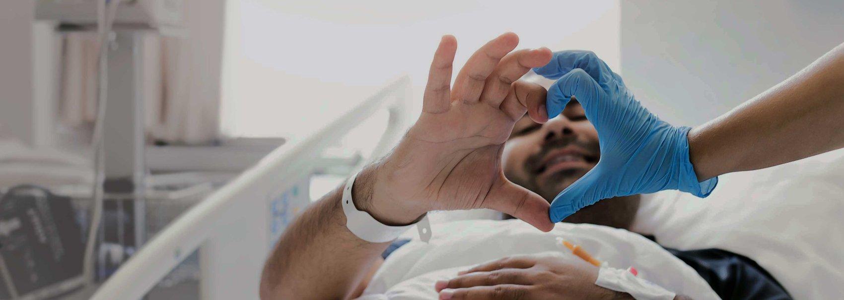 Trabajador sanitario y paciente haciendo una forma de corazón con las manos